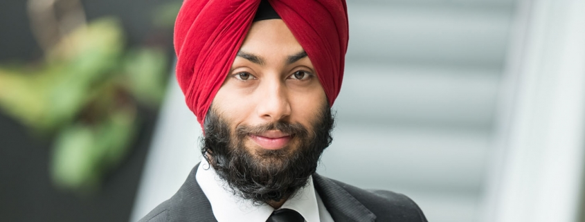 Young indian businessman in turban is looking at camera.