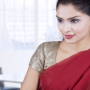 Attractive indian young businesswoman wearing traditional clothes and working with laptop computer
