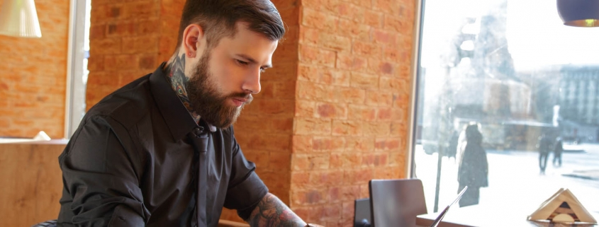 Bearded tattooed man using a laptop and drinks coffee in a cafe.