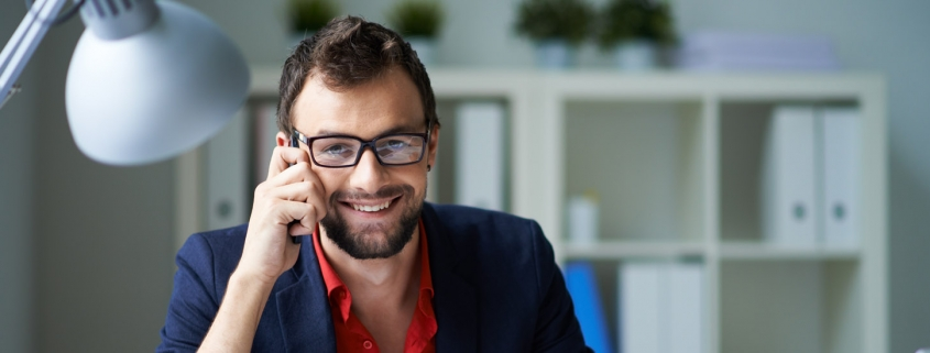 Handsome businessman speaking on the phone and working with laptop in office