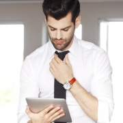 Portrait of confident financial assistant standing at office next to his workplace and holding digital tablet in hand. Youn professional working email.