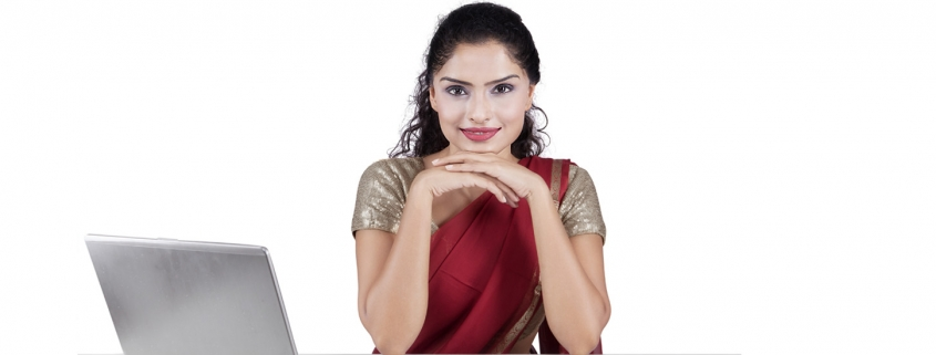 Portrait of indian young businesswoman smiling at the camera while wearing traditional clothes with laptop and financial chart on desk